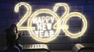 Une femme pose devant une inscription célébrant le passage à la nouvelle année, le 1er janvier 2020 à Séoul (Corée du Sud). (JUNG YEON-JE / AFP)