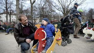 Un homme en congé paternité s'occupe de son enfant dans un parc (JONATHAN NACKSTRAND / AFP)