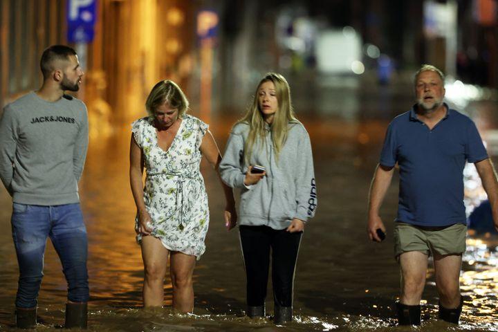 Des personnes traversent une rue inondée à Namur, le 24 juillet 2021. (DURSUN AYDEMIR / ANADOLU AGENCY / AFP)