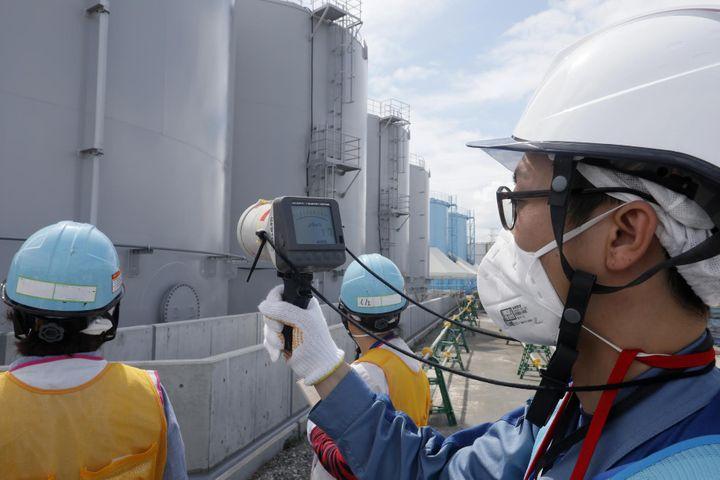 Un employé de Tepco mesurant la radioactivité devant des citernes contenant de l'eau contaminée par des éléments radioactifs,le27 juillet 2018, sur le site de la centrale nucléaire accidentée de Fukushima (Japon). (KIMIMASA MAYAMA / AFP)