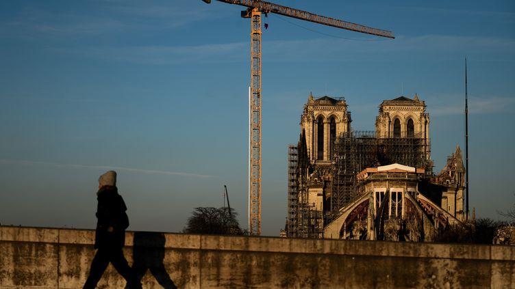 Un passant marche sur les quais, Notre-Dame de Paris en fond, le 6 janvier 2020. (PHILIPPE LOPEZ / AFP)