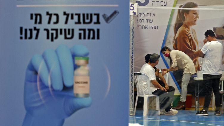 Des Israéliens reçoivent une injection du vaccin de Pfizer-BioNTech, le 4 février 2021, dans un gymnase d'Hod Hasharon (Israël). (JACK GUEZ / AFP)