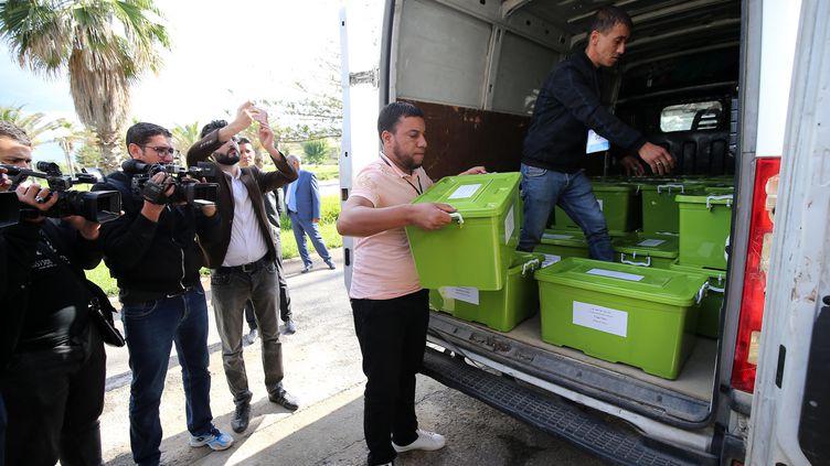 Des employés portent des cartons de 60 000 signatures de citoyens, nécessaires à la candidature de l'ancien Premier ministre algérien Abdelmadjid Tebboune, à l'Autorité électorale nationale indépendante à Alger, le 26 octobre 2019. (BILLAL BENSALEM / NURPHOTO)