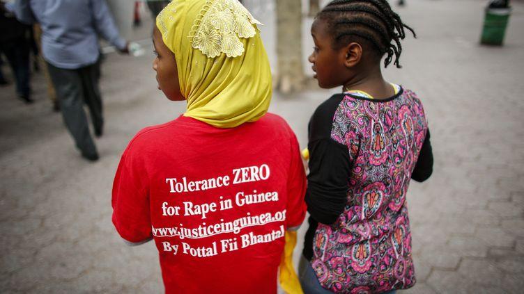 Deux fillettes observent une manifestation organisée par une ONG guinénne devant le siège de l'ONU à New York, le 28 septembre 2016, pour dénoncer la culture du viol en Guinée. (KENA BETANCUR / AFP)