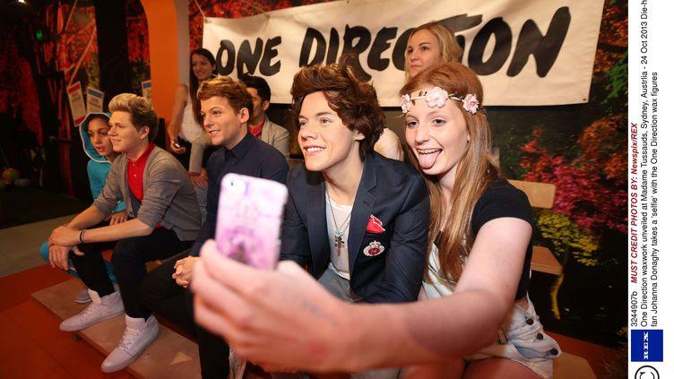 Une adolescente se prend en photo avec les statues de cire du groupe britannique One Direction, au musée de Madame Tussauds, à Sydney (Australie). (NEWSPIX / REX / SIPA )