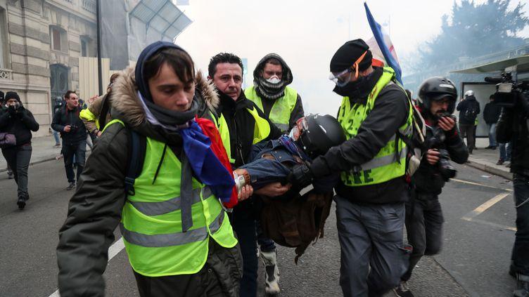 """Des """"gilets jaunes"""" portent secours à un blessé, le 5 janvier. (ZAKARIA ABDELKAFI / AFP)"""