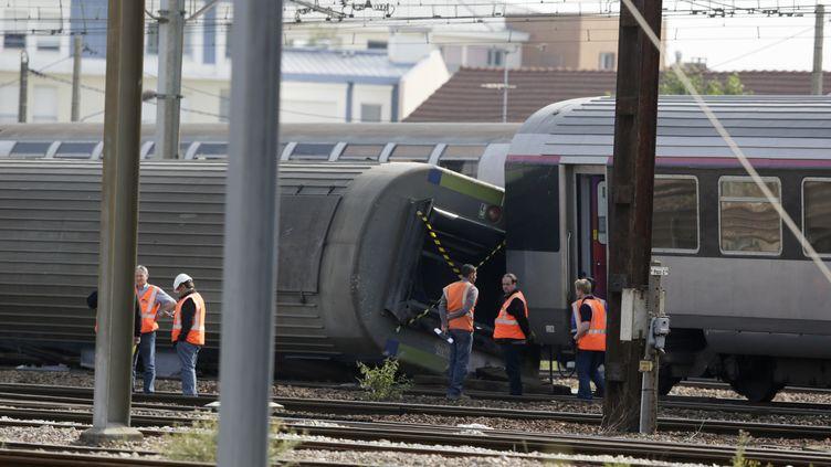 Des inspecteurs étudient l'un des wagons qui a déraillé à Brétigny-sur-Orge (Essonne), le 13 juillet 2013, au lendemain de la catastrophe ferroviaire qui a fait 7 morts et une trentaine de blessés. (KENZO TRIBOUILLARD / AFP)