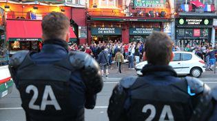 Des policiers surveillent des supporters de football, le 14 juin à Lille (Nord). (VITALIY BELOUSOV / SPUTNIK / AFP)