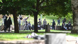 Des personnes sont assises sur des bancs après avoir été relogées près de la Porte de la Villette, dans le nord de Paris, le 24 septembre 2021, après une opération de police visant à expulser les consommateurs de crack dans le quartier des jardins d'Eole. (CHRISTOPHE ARCHAMBAULT / AFP)
