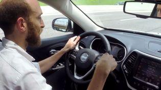 Le journaliste Andy Greenberg, du site américain Wired, au volant d'une voiture en train d'être piratée par deux hackers, dans une vidéo publiée le 21 juillet 2015. (WIRED / YOUTUBE)