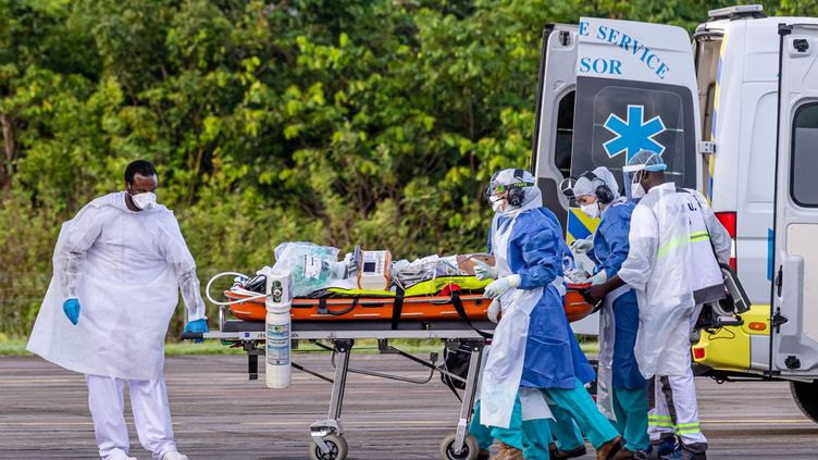 Le personnel médical transporte un patient infecté par le nouveau coronavirus dans un Airbus A400M sur la base aérienne guyanaise 367 à Matoury, près de Cayenne (Guyane), le 28 juin 2020. (JODY AMIET / AFP)