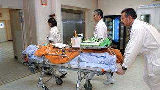 Un brancardier, un médecin et une externe, procèdent le 20 novembre 2001 au transfert en ambulance d'un malade maintenu en réanimation vers le service de radiologie de l'hôpital général de Dijon. (ERIC FEFERBERG / AFP)