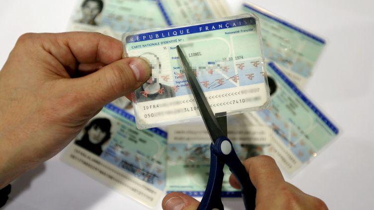 Un homme découpe une carte d'identité. (photo d'illustration) (MAXPPP)