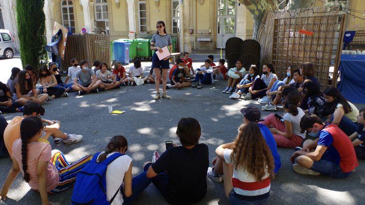 Collégiens en rond autour d'Agathe, animatrice, pour le bilan de leur séjour au Festival d'Avignon. (JEREMIE LAURENT-KAYSEN)