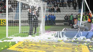 Les délégués du match Auxerre-Montpellier enlèvent les balles de tennis et le papier toilette lancés par les supporters d'Auxerre, le 20 mai 2012. (MICHEL PIEYRE / MAXPPP)