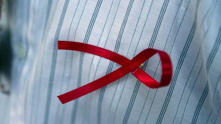 Leruban rouge, symbole international que l'on accroche sur ses vêtements pour afficher sa solidarité vis-à-vis des victimes duVIHet du Sida. Ici porté sur un homme, en décembre 2015 dans la ville de Mexico (Mexique). (HUGO BORGES / NOTIMEX)