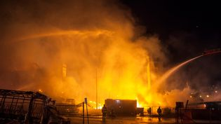 Des pompiers s'activent pour éteindre les flammes, le 28 avril 2015 à Baltimore (Etats-Unis). (SAMUEL CORUM / ANADOLU AGENCY / AFP)