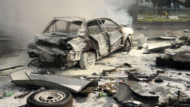 Une voiture brûlée après l'attentat près du siège du parti Baas, le parti de Bachar Al-Assad, à Damas (Syrie), le 21 février 2013. (SANA / AFP)