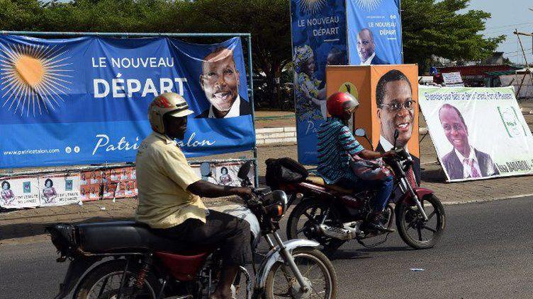 Le 3 mars 2016 à Cotonou: des motocyclistes passent devant les affiches des candidats Patrice Talon et Pascal Koupaki, candidats de la présidentielle béninoise dont le premier tour se tient le 6 mars 2016. (PIUS UTOMI EKPEI / AFP)