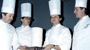 """Joël Robuchon (2e en partant de la droite) reçoit le prix du """"cuisinier de l'année"""", à Paris, le 23 novembre 1987. (JOEL ROBINE / AFP)"""