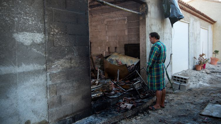 Un habitant de Vitrolles (Bouches-du-Rhône) devant sa maison ravagée parles flammes, jeudi 11 août 2016. (BERTRAND LANGLOIS / AFP)