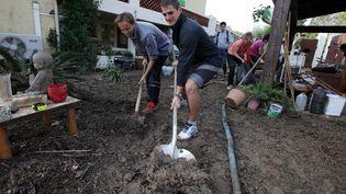 Familles et voisins s'affairent pour nettoyerles jardins ravagés par les pluies torrentielles tombées le 3 octobre 2015, à Biot (Alpes-Maritimes). (MAXPPP)