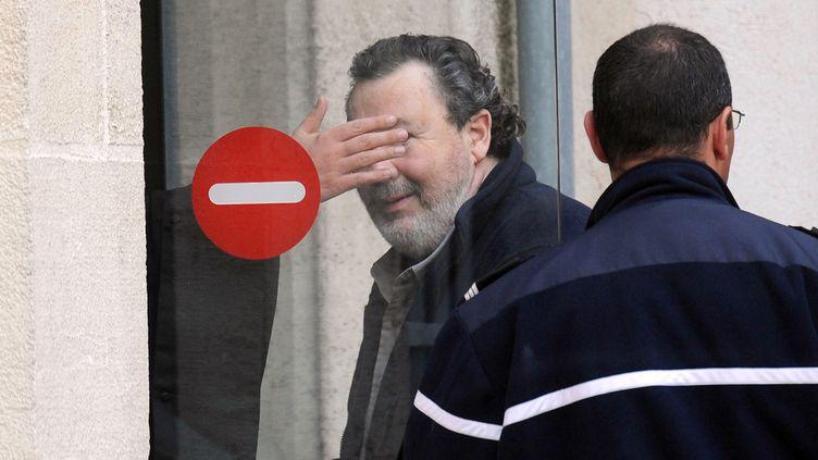 Philippe Berre (C), dont le visage est camouflé par la main de son avocat, devant le tribunal correctionnel de La Rochelle (Charente-Maritime), le 5 avril 2012. (XAVIER LEOTY / AFP)