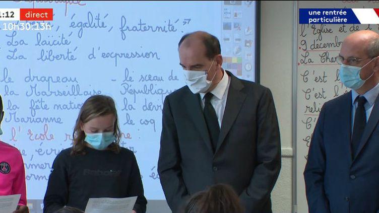 Jean Castex, Premier ministre et Jean-Michel Blanquer, ministre de l'Education nationale, regardent des élèves lirent la lettre aux instituteurs et institutrices de Jean Jaurès, dans une école de Conflans-Sainte-Honorine (Yvelines), le 2 novembre 2020. (CAPTURE ECRAN / OUVREZ LE 1 / FRANCEINFO (CANAL 27))