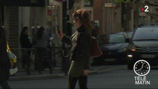 Une femme regardant son smarphone en traversant. (France 2)