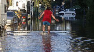 Un homme se fraye un chemin dans les rues inondées de Biot, le 4 octobre 2015, dans les Alpes-Maritimes. (ERIC GAILLARD / REUTERS)