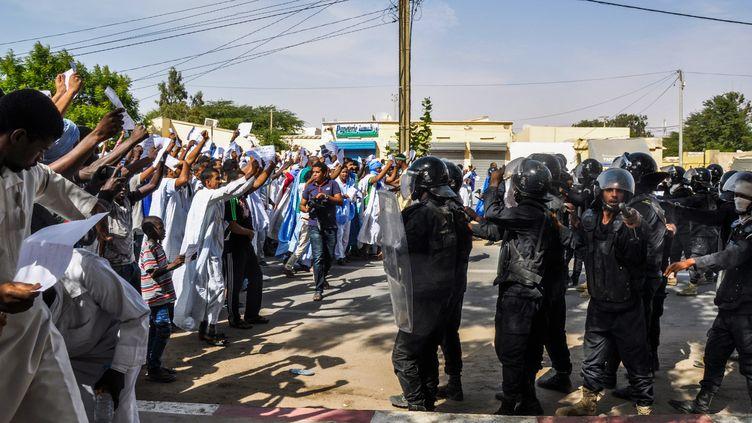 Des manifestants font face à la police anti-émeute, à Nouakchott, le 10 novembre 2017, pour protester contre la décision de la cour d'appel de Nouadhibou de commuer la peine de mort pour apostasie prononcée contre Ould Mkheitir en deux ans de prison. (STR / AFP)