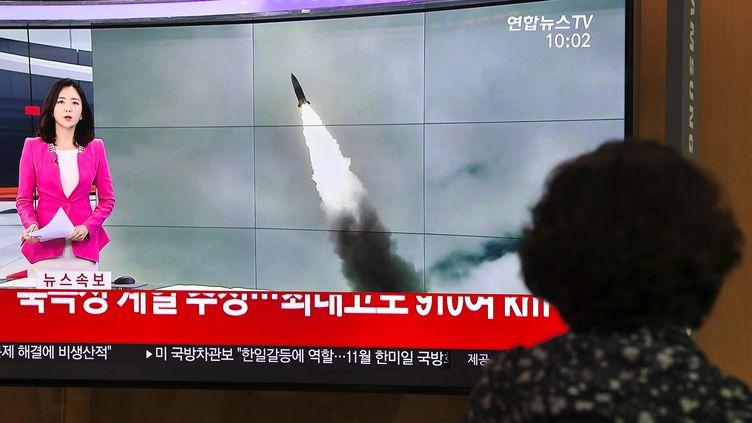 Une passante regarde une chaîne de télévision sud-coréenne évoquer le nouveau tir de missile effectué par Pyongyang, le 2 octobre 2019 à Séoul (Corée du Sud). (JUNG YEON-JE / AFP)