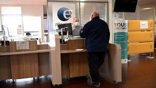 Un membre du personnel s'entretient avec une personne dans une agencePôle Emploi à Marseille, le 14 décembre 2020. (NICOLAS TUCAT / AFP)