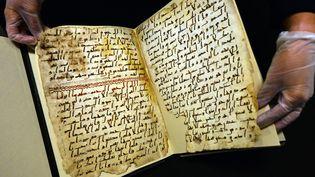 Une conservatrice de l'université de Birmingham (Royaume-Uni) montre, le 22 juillet 2015, de très anciens fragments du Coran, retrouvés dans la bibliothèque de l'établissement. (PAUL ELLIS / AFP)