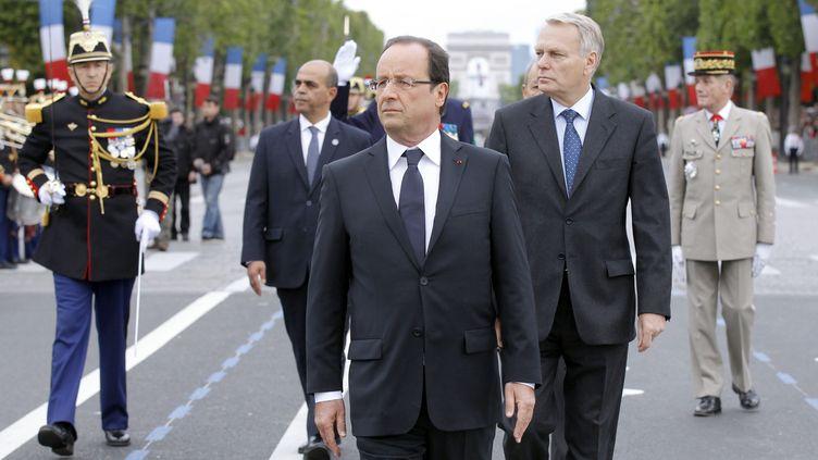 Le président François Hollande accompagné du Premier ministre Jean-Marc Ayrault lors du défilé du 14-Juillet sur les Champs-Elysées à Paris. (BENOIT TESSIER / POOL)