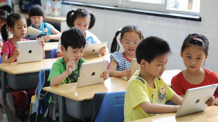 La tablette d'Apple est déjà utilisée dans d'autres écoles à travers le monde, comme celle-ci à Hangzhou (Chine). (JU HUANZONG / XINHUA)
