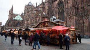 Des passants se rendent sur le marché de Noël, deux jours après l'attentat de Strasbourg, le 14 décembre 2018. (MARIJAN MURAT / DPA / AFP)