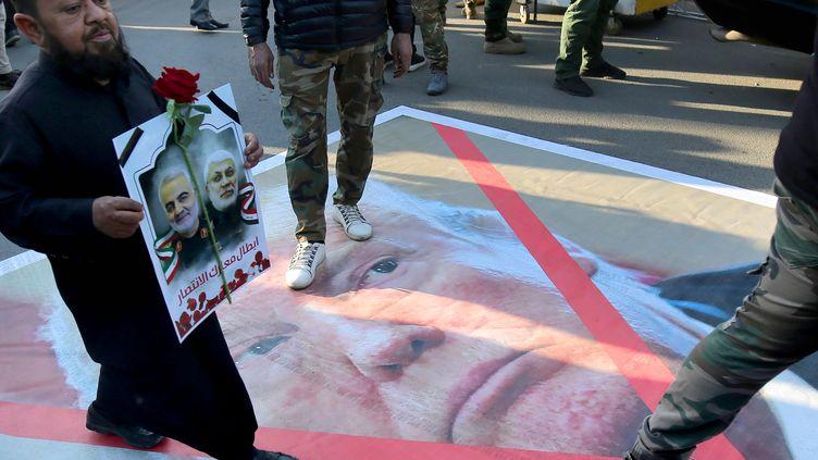 Un portrait du président américain Donald Trump piétiné le 6 janvier 2020 à Bagdad (Irak), lors d'une procession en hommage au général iranien Qassem Soleimani, tué par une frappe américaine sur la capitale irakienne. (AHMAD AL-RUBAYE / AFP)