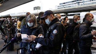 Des policiers effectuent des contrôles sur les passagers débarquant d'un train en provenance de Mulhouse (Haut-Rhin), à la gare de Lyon à Paris,le 26 mars 2021. (THOMAS COEX / AFP)