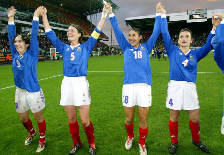 Corinne Diacre, deuxième en partant de la gauche, célèbre la victoire des Bleues lors du match de barrage contre l'Angleterre, à Saint-Etienne, le 16 novembre 2002. (PHILIPPE MERLE / AFP)