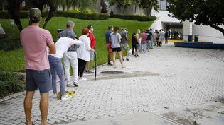 Des dizaines d'électeurs patientent pour pouvoir voter à l'élection présidentielle dans un bureau de vote anticipé à Miami (Etats-Unis), le 19 octobre 2020. (EVA MARIE UZCATEGUI / AFP)