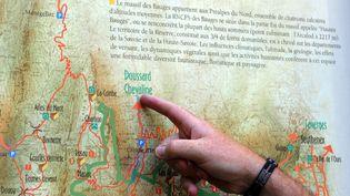 Un homme pointe la ville de Chevaline (Haute-Savoie) sur une carte, là, où a eu lieu en 2012 les meurtres de trois touristes britanniques et d'un cycliste. (PHILIPPE MERLE / AFP)