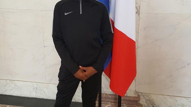 Yannel pose devant des drapeaux à l'Elysée, le 10 juillet 2018, avant de s'envoler pour Saint-Pétersbourg où il assistera au match France-Belgique aux côtés d'Emmanuel Macron. (DR)