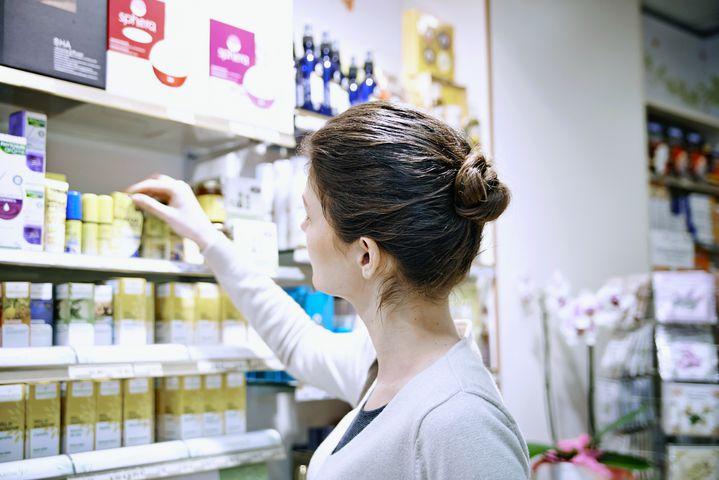 Photo d'illustration. Une femme choisit une huile essentielle en pharmacie. (ALICE S. / BSIP / AFP)