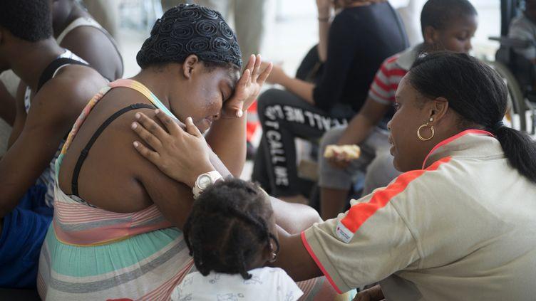 Une membre de la Croix-Rouge réconforte une sinistrée de Saint-Martin, le 9 septembre 2017, à l'aéroport de Pointe-à-Pitre, en Guadeloupe. (HELENE VALENZUELA / AFP)