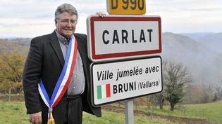 Alain Cousin, alorsmaire de Carlat (Cantal),pose devant le panneau d'entrée de son village, jumelé avec Bruni (Italie), en clin d'œil à la Première dame de l'époque, le 21 novembre 2011. (THIERRY ZOCCOLAN / AFP)