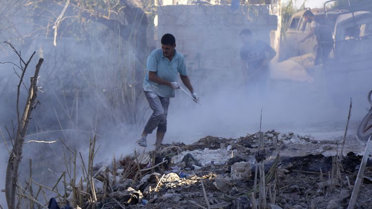 Des Syriens tentent d'éteindre un feu provoqué par un bombardement de l'aviation russe dans la province d'Idlib en Syrie, le 4 septembre 2018. (ZEIN AL RIFAI / AFP)