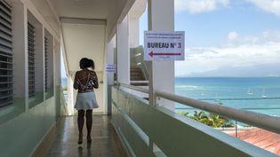 Une femme arrive à son bureau de vote pour le second tour de l'élection présidentielle, le 6 mai 2017 au Gosier, en Guadeloupe. (HELENE VALENZUELA / AFP)