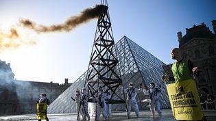 Une vingtaine d'activistes de Greenpeace ont manifesté devant le Louvre à Paris pourprotester contre le partenariat entre le musée et TotalEnergies, le 6 octobre 2021. (ANNE-CHRISTINE POUJOULAT / AFP)