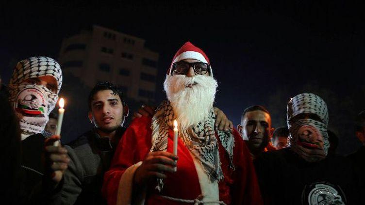 Des hommes masqués en compagnie d'un homme déguisé en père Noël dans la ville de Gaza, le 25 décembre 2015, lors d'un rassemblement en hommage à des Palestiniens tués par des tirs israéliens. (AFP/ Momen Faiz/NurPhoto)